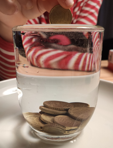 Why if the glass is full and we still put coins in it, the water does not spill?